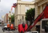 Imatge dels treballs d'instal·lació de la nova il·luminació ornamental a la façana de l'Escola Pompeu Fabra