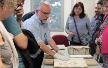 L'arxiver comarcal, en Sabí Peris, comenta els diferents llibres històrics: actes municipals, cadastre, expedients de foment...